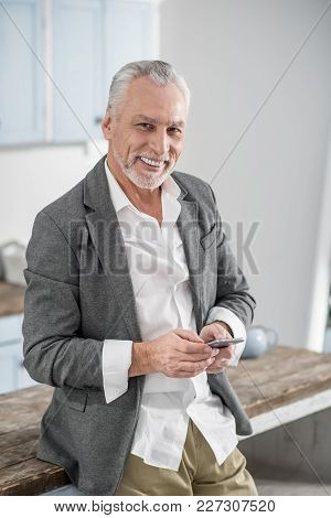 Look At Me. Positive Delighted Male Person Leaning On Table And Keeping Smile On Face While Looking