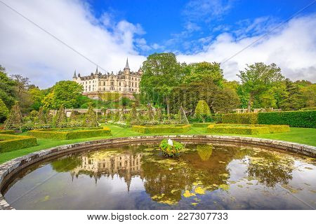 Scenic Dunrobin Castle Fountain Reflecting The Dunrobin Castle In The Garden Park That Surrounds It.