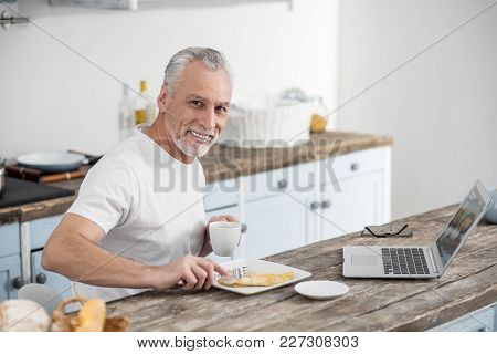 Healthy Food. Handsome Mature Man Keeping Smile On His Face And Looking At Camera While Eating Omele