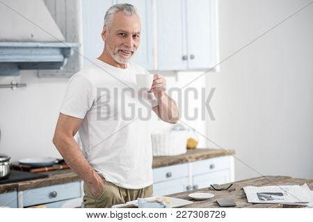 Have Free Time. Positive Delighted Male Person Smiling While Looking Forward And Keeping Right Hand