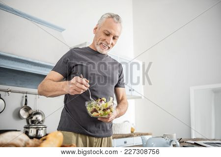 Eat Vitamins. Cheerful Pensioner Being In The Kitchen And Keeping Smile On His Face While Mixing Sal