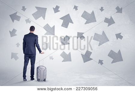 Businessman with back walking away with higgledy-piggledy arrows around