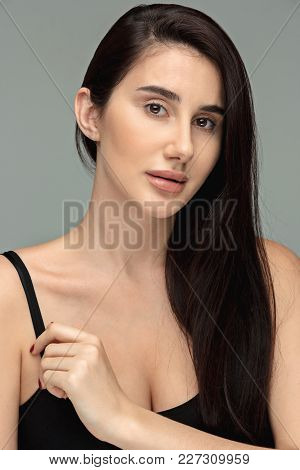 I Am Young And Pretty. Portrait Of Beautiful Dark-haired Girl On Gray Studio Background. Fashion Cau