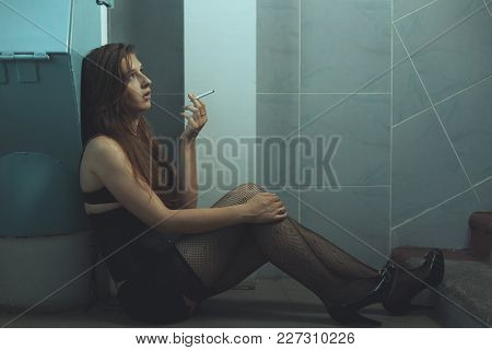 Young Woman A Drug Addict Sitting On The Floor Under The Euphoria.