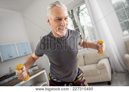 Healthy Lifestyle. Sporty Man Keeping Smile On His Face And Holding Dumbbells In Both Hands While Th