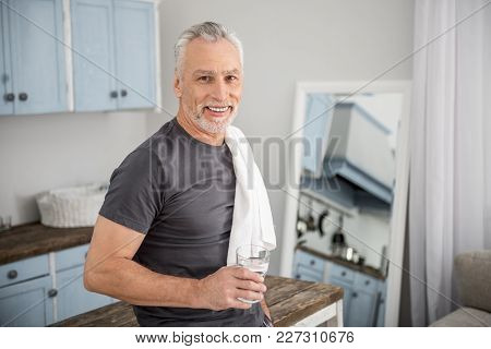 Need To Refresh. Cheerful Mature Male Keeping Smile On His Face And Holding Glass With Water While H