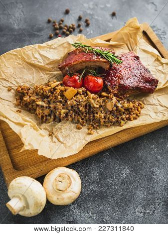 Barbecued Spare Ribs, Buckwheat With Mushroom And Tomatoes On Wooden Cutting Board.