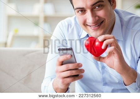 Young man chatting with his sweetheart over mobile phone