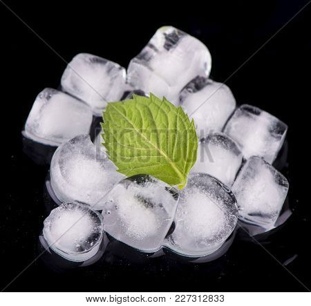 Ice Cube With Mint Leaves On Black Background