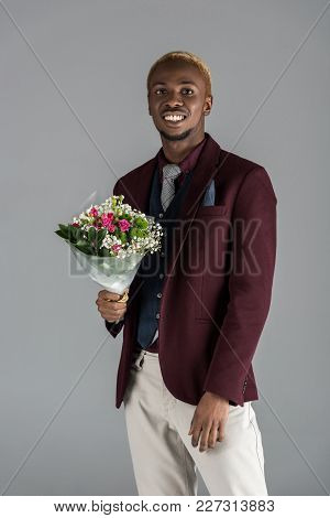 Smiling African American Man With Bouquet In Hand Looking At Camera Isolated On Grey