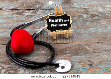 A Board With The Word Health And Wellness And Stethoscope. The Concept Of Medicine.