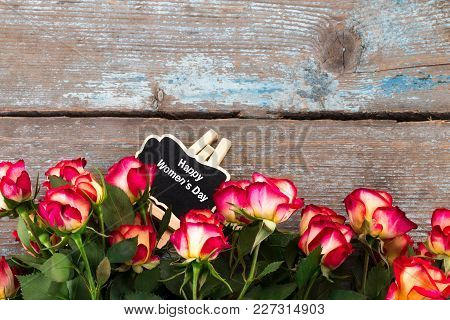 Background With Roses And Chalkboard On Wooden Table. Top View With Copy Space.