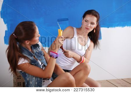Two Beautiful young woman doing wall painting, sitting. Two Beautiful young woman.