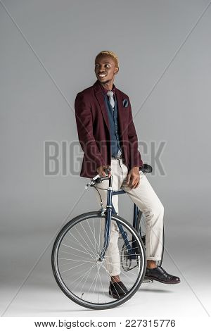 Smiling African Man Sitting On Bike And Looking Away On Grey Background