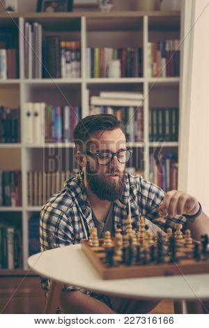 Man Playing Chess At Home, Enjoying His Leisure Time