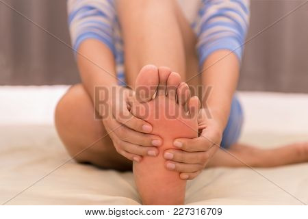 Woman Massaging Her Foots On The Bed After Exercise.