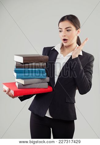 Young Female Student With Many Colorful Books