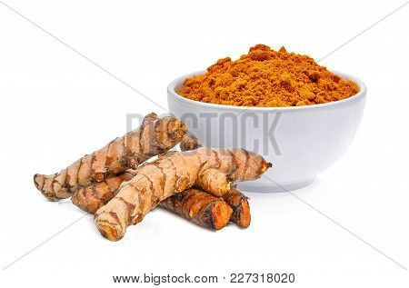 Turmeric Powder In White Bowl With Turmeric Roots Isolated On White Background