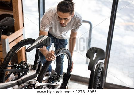 Man Working On A Bicycle Wheel In A Repair Shop. Worker Fixing A Bicycle In Workshop.