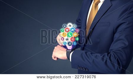 Businessman wearing smartwatch with colored application symbols on it.