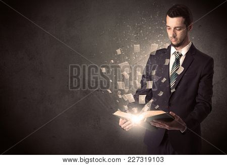 Man holding a book with document symbols around.