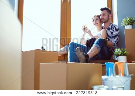 Couple moving in house sitting on the windowsill. Couple