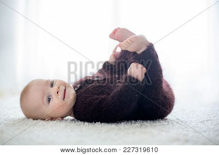Little Cute Baby Boy, Dressed In Handmade Knitted Brown Teddy Bear Overall, Playing At Home In Sunny