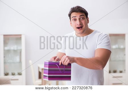 Young man with gift bag at home preparing suprise for wife