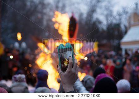 Yoshkar-ola, Russia - February 18, 2018 Maslenitsa Fest. Shooting A Video On The Phone Burning Stuff