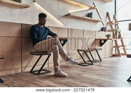 Another Business Message. Handsome Young Man Using His Smart Phone While Sitting In The Creative Wor