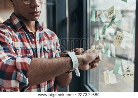 Keeping An Eye On Time. Close Up Of Young Man Checking The Time While Standing Near The Window
