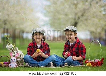 Two Children, Boy Brothers, Having Fun With Easter Eggs In The Park