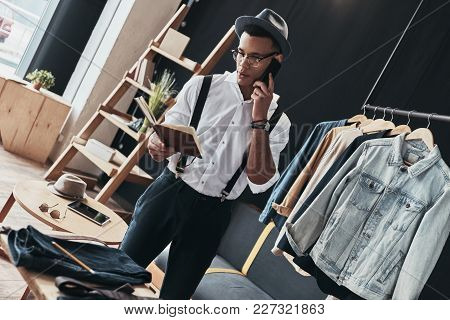 Discussing Details. Good Looking Young Man Talking On Smart Phone While Standing In The Showroom