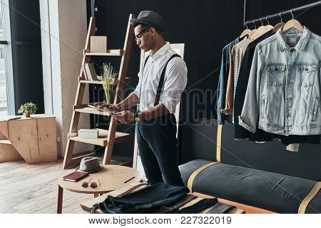 Sharing New Ideas. Serious Young Man Working Using Digital Tablet While Standing In The Showroom