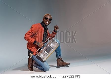 Handsome Stylish Young African American Man Holding Silver Tape Recorder And Smiling On Grey