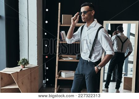 Looking Just Perfect. Handsome Young Man Adjusting Eyewear And Keeping Hand In Pocket While Spending
