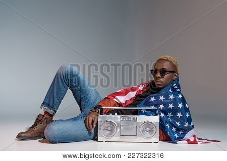 Young African American Man With Us Flag On Shoulders Lying With Silver Tape Recorder On Grey