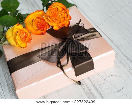 Beautiful Gift For The Holiday And A Bouquet Of Orange Roses On The Table