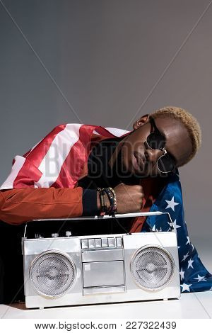 Young African American Man With Us Flag On Shoulders Holding Silver Tape Recorder On Grey