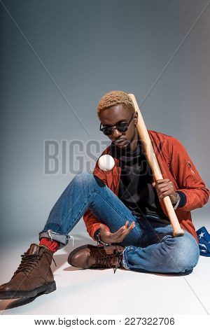 Young African American Man Sitting And Holding Baseball Bat With Ball On Grey