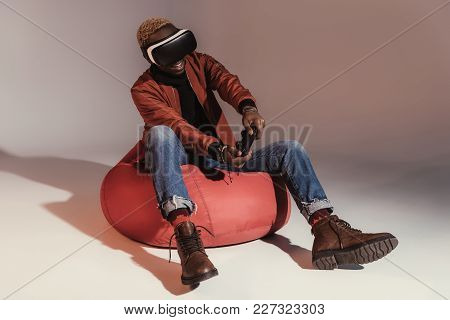 Young African American Man In Virtual Reality Headset Playing With Joystick While Sitting On Bean Ba