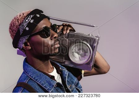 Stylish Young African American Man In Sunglasses Holding Tape Recorder On Shoulder And Looking Away