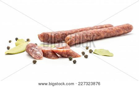 Two Hungarian Dry Sausages Pepperoni With Black Pepper Bay Leaves And Cut Pieces Isolated On White B