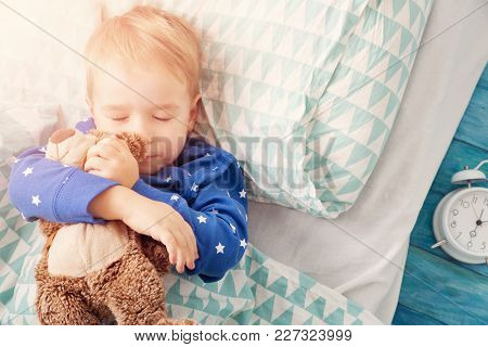 Three Years Old Child Sleeping In Bed On Pillow With Alarm Clock And A Teddy Bear