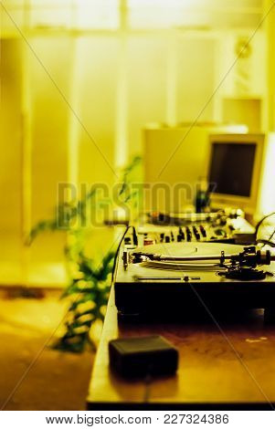Dj Turntables On A Desk In A Yellow Lit Room