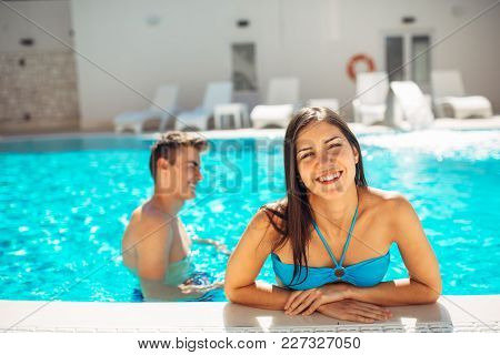 Smiling Cheerful Woman Swimming In A Clear Pool On A Sunny Day.having Fun On Vacation Pool Party.fri