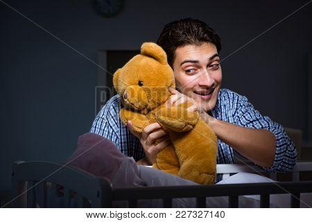 Happy dad looking after newborn baby at night