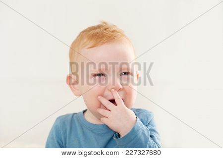 The Baby Cries With A Hand To His Mouth