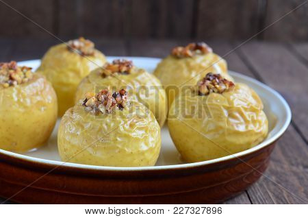 Baked And Stuffed Apples On Wood Boards And Fir Cones In The Background