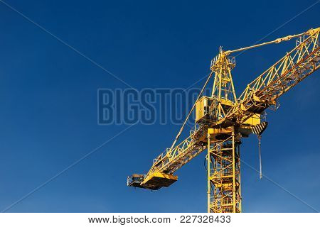 Construction Crane Tower On Background Of  Blue Sky. Crane And Building Working Progress On Construc